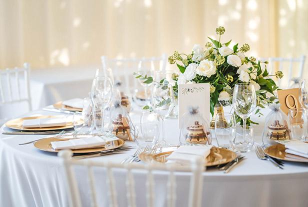 gedeckter Tisch mit prachtvoller Blumendeko in weiß