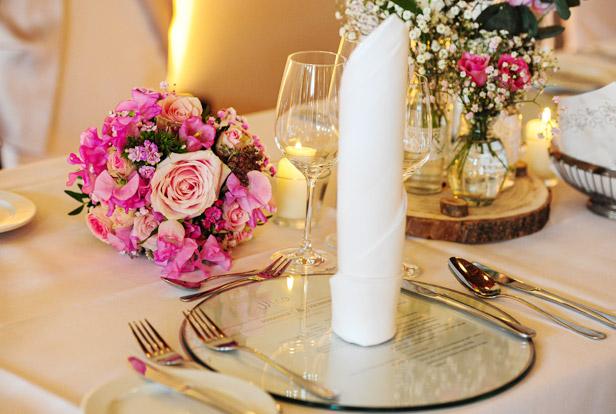 Tisch mit Blumen und Glasuntersetzer