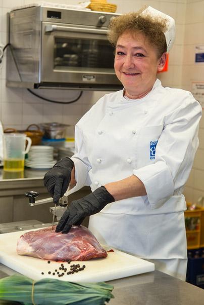Mitarbeiterin von food et event in der Küche am Fleisch schneiden
