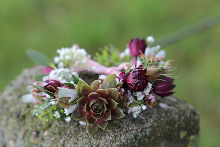 Blumenkranz liegt auf einem Stein