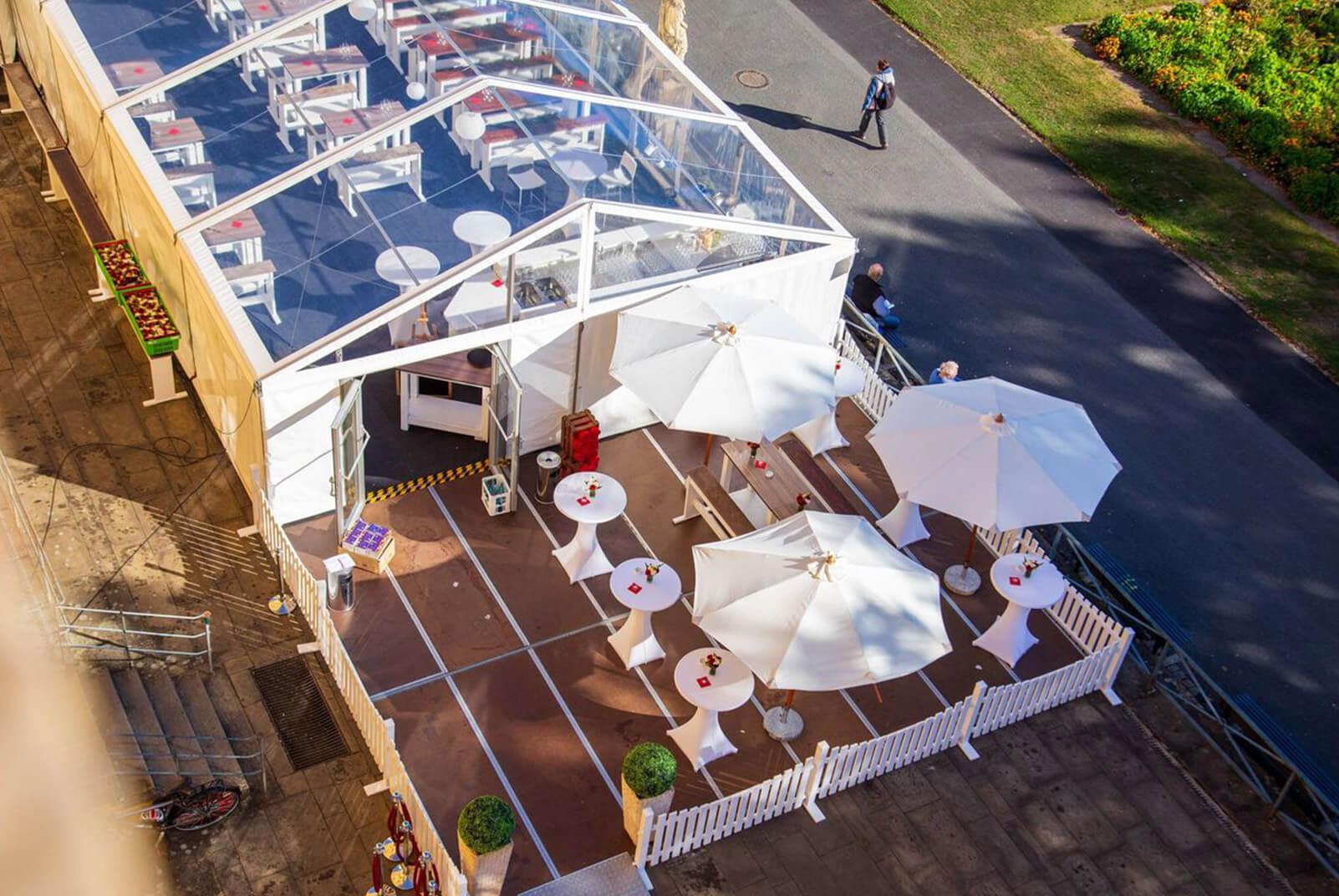 weißes Zelt mit weißen Schirmen und Stehtischen davor
