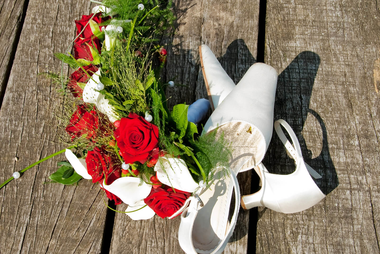 Brautschuhe und Brautstrauß mit roten Rosen