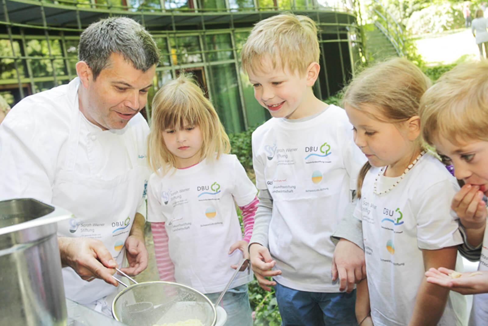Kinder beobachten Helge Weber beim kochen