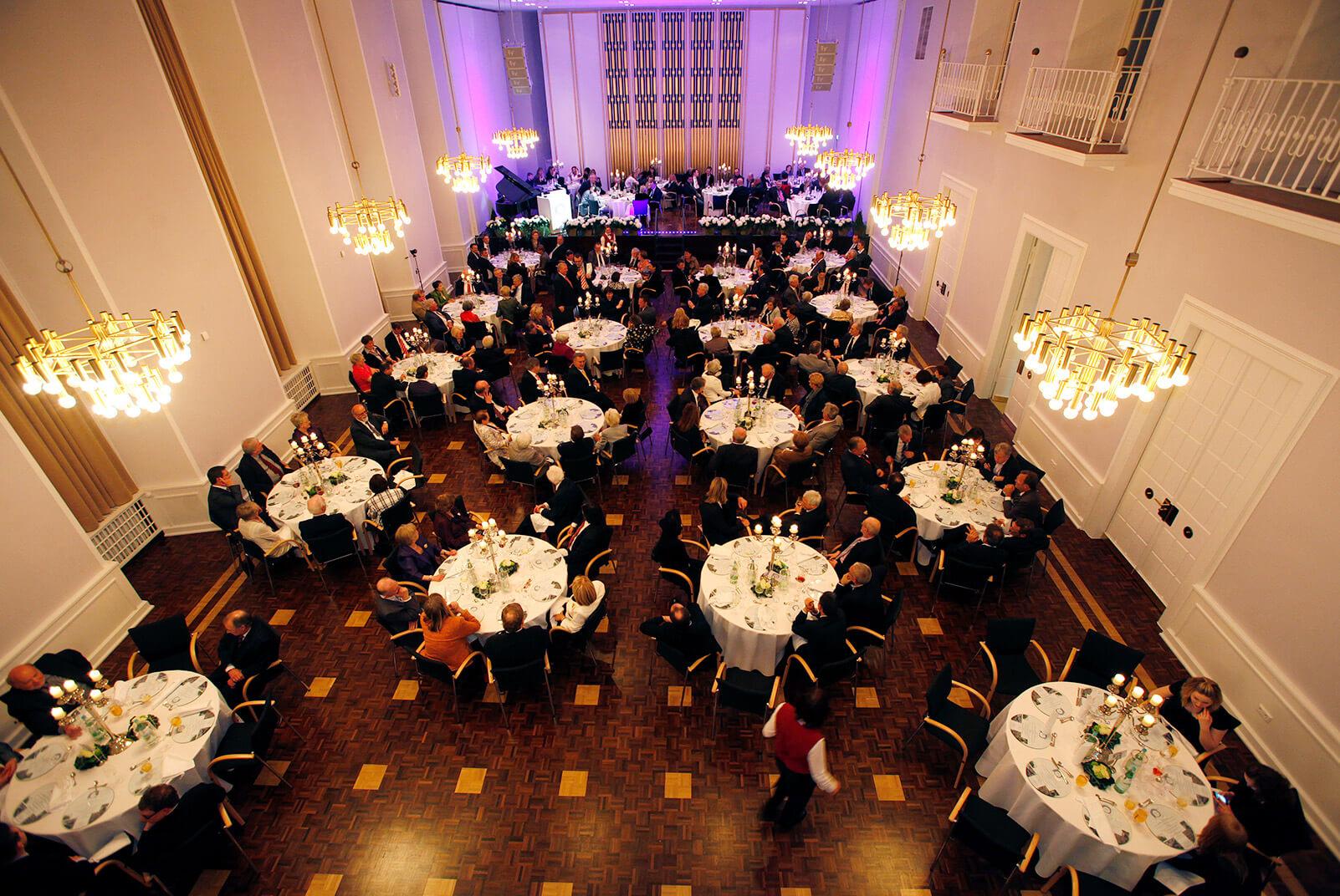 Festsaal mit vielen runden Tischen und Menschen