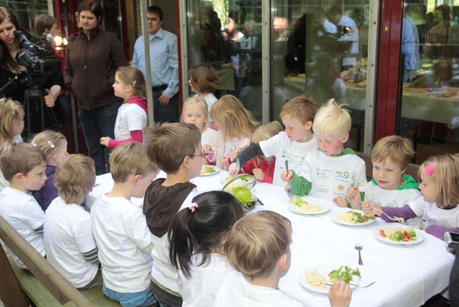Kinder sitzen am Tisch und essen