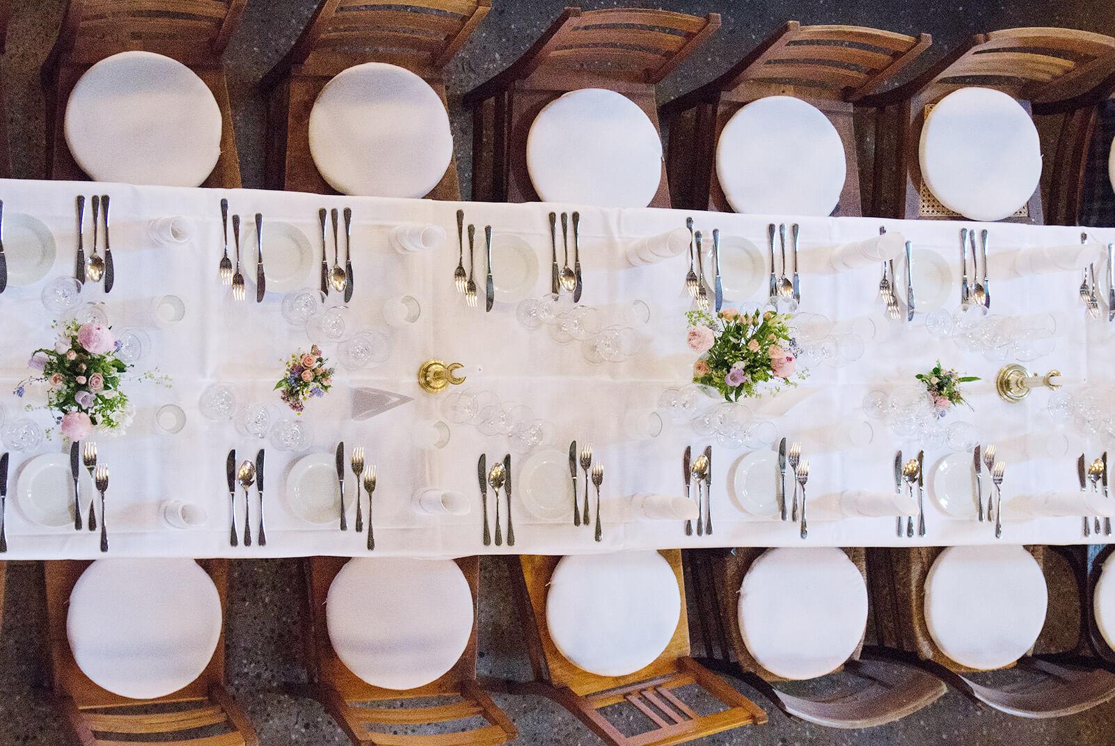 lange gedeckte Tafel mit schöner Blumdendeko
