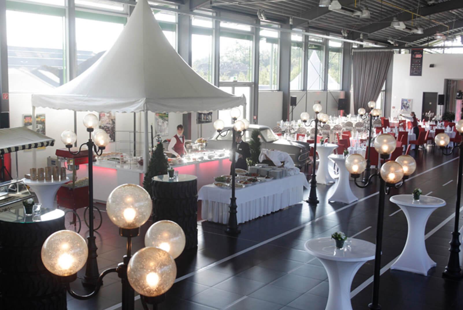 Buffettzelt und gedeckte Tische in einer Messehalle