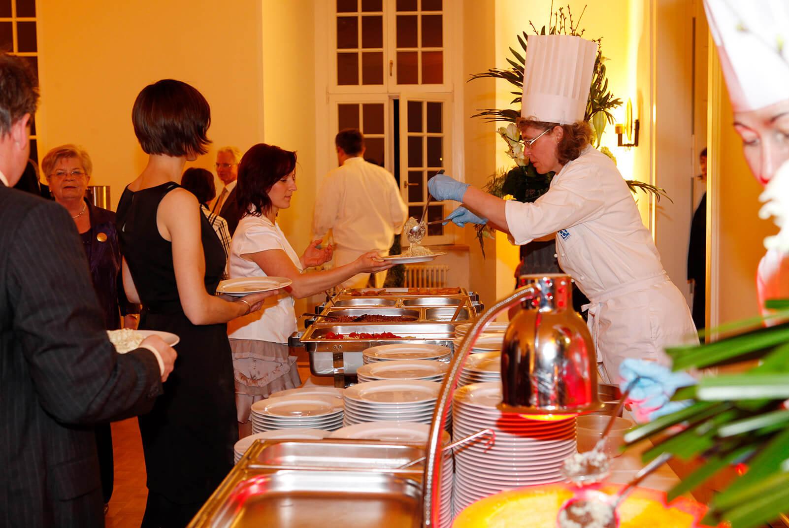 Menschen am Buffett, Mitarbeiterin von food et event serviert