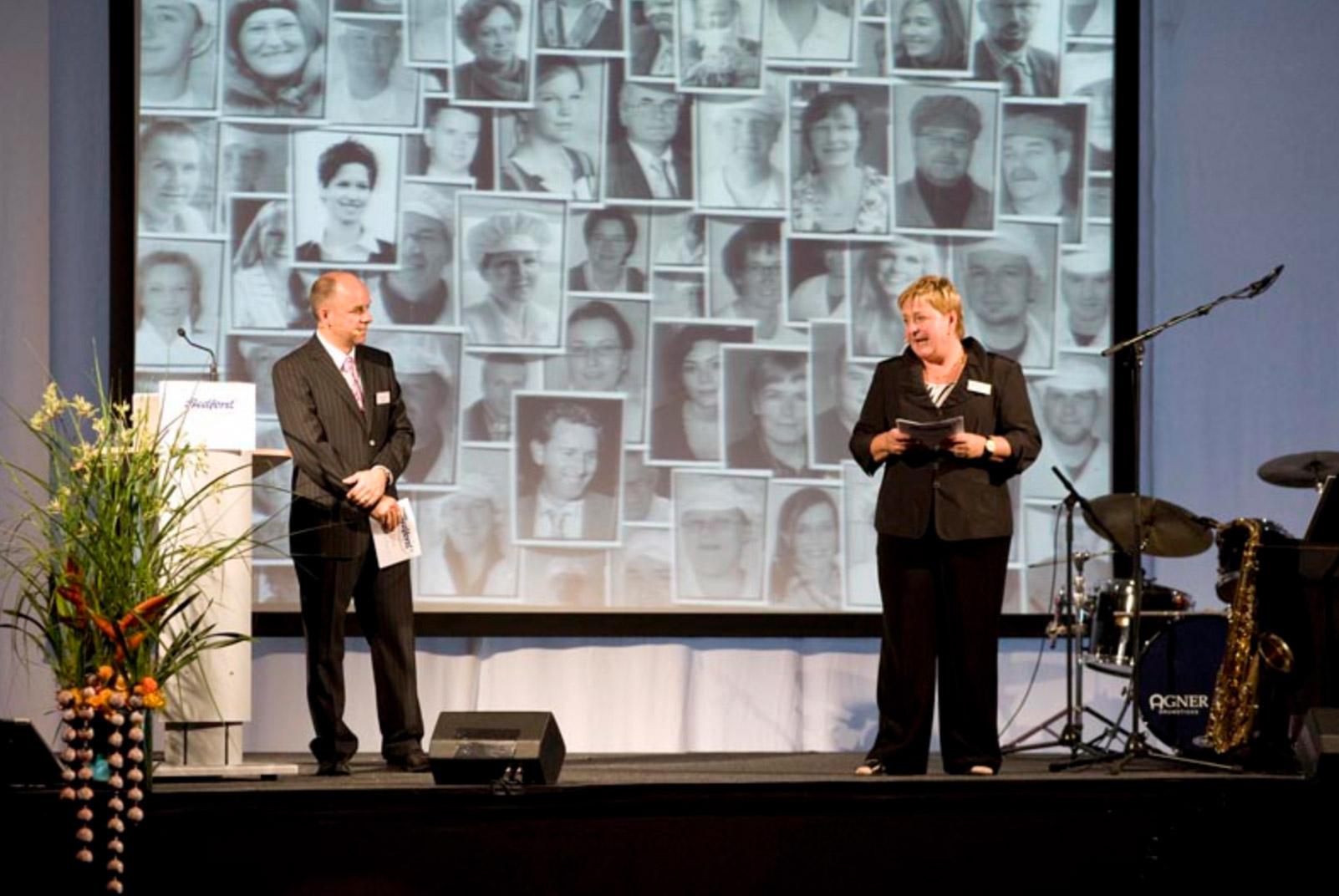 ein Mann und eine Frau auf einer Bühne halten eine Rede