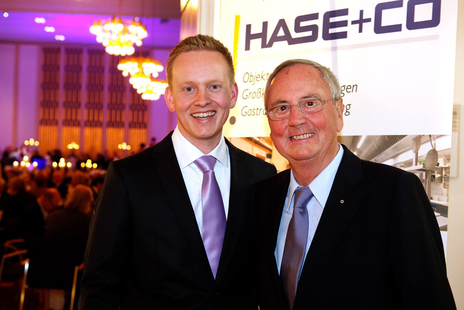 zwei Männer vor einiem Schild von Hase+Co