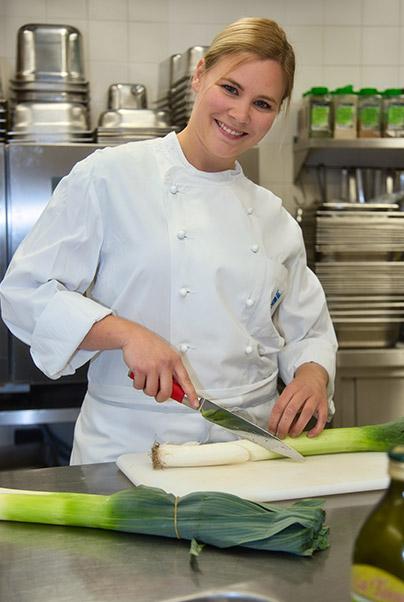 Mitarbeiterin von food et event am Lauch schneiden