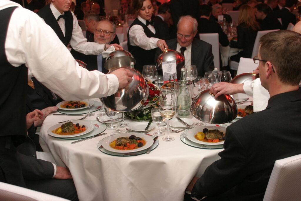 Männer an einem runden Tisch bekommen ihr Essen serviert